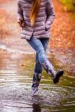 Gladlynt flicka i gummistöveler som hoppar på pölar efter regn arkivfoton
