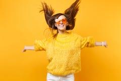 Gladlynt flicka i pälströjan, orange exponeringsglas för hjärta som omkring bedrar i studiohopp med flödande hår som isoleras på  royaltyfri bild