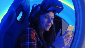 Gladlynt flicka i virtuell verklighethörlurar med mikrofon som kontrollerar hennes selfies på telefonen Royaltyfria Bilder