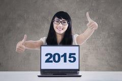 Gladlynt flicka med bärbar datorvisningtummar-upp Arkivfoton