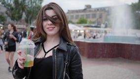 Gladlynt flicka med coctailen i händer, attraktiv kvinna av långt hår, brunett för unga kvinnor utomhus, lycklig kvinnlig stock video