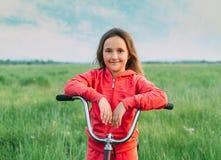 Gladlynt flicka med en cykel i sommar Arkivfoto