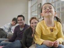 Gladlynt flicka med familjsammanträde på soffan Royaltyfri Fotografi