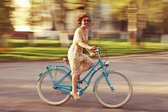 Gladlynt flicka på en cykel Royaltyfri Fotografi