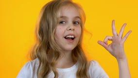 Gladlynt flicka som blinkar visa det ok tecknet som ?r lyckligt med gods f?r barn, n?rbild stock video