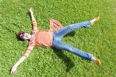 Gladlynt flicka som faller på gräset med hennes utsträckta armar royaltyfri bild