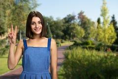 Gladlynt flicka som gör en gest utomhus- fred royaltyfri fotografi