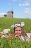 Gladlynt flicka som lägger på filten i fältet Royaltyfri Bild