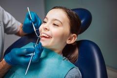 Gladlynt flicka som sitter i tand- stol i rum Hon visar tänder Tandläkare som gör kontrollen-upp med den lilla spegeln och hjälpm royaltyfri bild
