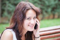 Gladlynt flicka som talar på mobiltelefonen Fotografering för Bildbyråer