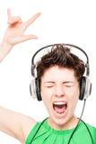 Gladlynt flicka som tycker om en vit bakgrundsmusik på hörlurar Royaltyfria Foton