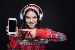 Gladlynt flicka som visar olika grejer till åhörarna arkivbild