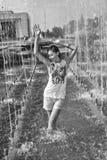 Gladlynt flickadans under strålar av vatten i stadsspringbrunn Arkivfoto
