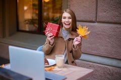 Gladlynt flickasammanträde i ett kafé som rymmer ett stupat höstblad och en gåvaask i hand och lyckligt ler Royaltyfri Fotografi