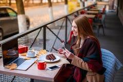 Gladlynt flickasammanträde i kafé med bärbara datorn som äter efterrätten och att le utanför I hösten Fotografering för Bildbyråer