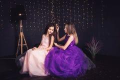 gladlynt flickvänner Två flickor kammar sig hår för ` som s sitter sidan - förbi - sid i studio på mörk bakgrund kopiera avstånd Arkivfoto
