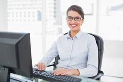 Gladlynt flott brun haired affärskvinnamaskinskrivning på en dator royaltyfri foto