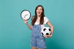 Gladlynt fotbollsfanjubel för ung kvinna upp det favorit- laget för service med fotbollbollen, rund klocka som isoleras på blått arkivbild
