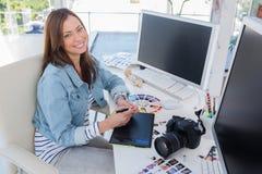 Gladlynt fotoredaktör som arbetar med en grafisk minnestavla Arkivbild