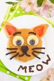 Gladlynt frukost - katten säger jamar pannkakor arkivfoto