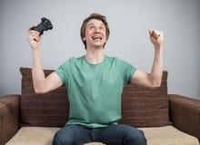 Gladlynt gamer på soffan fotografering för bildbyråer