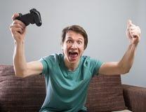 Gladlynt gamer på soffan royaltyfri foto