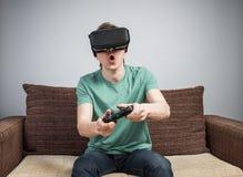 Gladlynt gamer på soffan royaltyfri fotografi