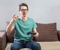Gladlynt gamer på soffan arkivbilder