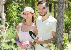 Gladlynt gift par i blommaträdgård Arkivbilder
