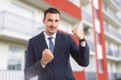 Gladlynt glad fastighetsmäklare- eller försäljningsman på hyreshusbackg royaltyfri bild