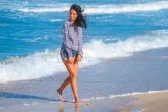 Gladlynt glad kvinnaspring längs stranden, begreppet av semestern och lopp royaltyfria foton