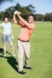 Gladlynt golfare som tar skottet Royaltyfri Foto