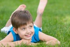 gladlynt grön lawn för pojke arkivfoto