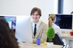Gladlynt grabb som framme sitter av den skrivbords- datoren royaltyfria foton