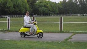 Gladlynt grabb som rider en sparkcykel arkivfilmer