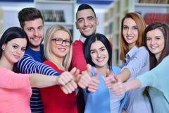 Gladlynt grupp av studenter som ler på kameran med tummar upp, framgång och lär begrepp Royaltyfri Bild