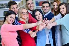 Gladlynt grupp av studenter som ler på kameran med tummar upp, framgång och lär begrepp Royaltyfria Foton