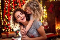Gladlynt gullig lockig liten flicka och hennes äldre syster som har gyckel som inomhus kramar nära julträd fotografering för bildbyråer