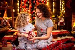 Gladlynt gullig lockig liten flicka och hennes äldre syster som utbyter gåvor royaltyfria foton
