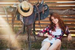 Gladlynt gullig rödhårig mancowgirl som vilar på ranchstaketet arkivfoto