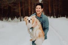 Gladlynt gullig skratta och le grabb i jeanskläder med hunden border collie som är röd på hans händer i snöig skogbegrepp fotografering för bildbyråer