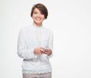 Gladlynt gulligt älskvärt innehav för ung kvinna och användamobiltelefon royaltyfria bilder