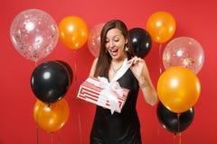 Gladlynt häpen ung flicka i svart klänning som firar, röd ask för öppning med gåvagåva på ljus röd bakgrundsluft arkivfoto