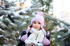 Gladlynt härlig flicka i lilavinterhatt Arkivfoto