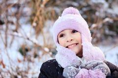 Gladlynt härlig flicka i lilavinterhatt Arkivfoton