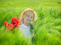 Gladlynt härlig flicka med en bukett av vallmo i ett fält av grön råg Fotografering för Bildbyråer