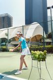 Gladlynt härlig kvinna som spelar tennis i en framkallad stad arkivbild
