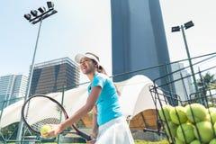 Gladlynt härlig kvinna som spelar tennis i en framkallad stad royaltyfri foto