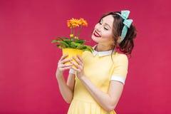 Gladlynt härlig ung kvinna som ler och rymmer blomman i kruka Royaltyfria Bilder