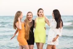 Gladlynt, härligt, lyckligt och unga flickor i trendiga och mång--färgglade klänningar på en bakgrund av havet Arkivfoto